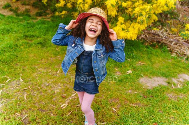 Веселый ребенок в соломенной шляпе с закрытыми глазами смеется на лугу против цветущего куста при дневном свете — стоковое фото