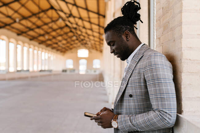 Бічний вид на добре одягненого афроамериканського чоловіка-підприємця з дредами в блокноті текстові повідомлення на мобільному телефоні — стокове фото