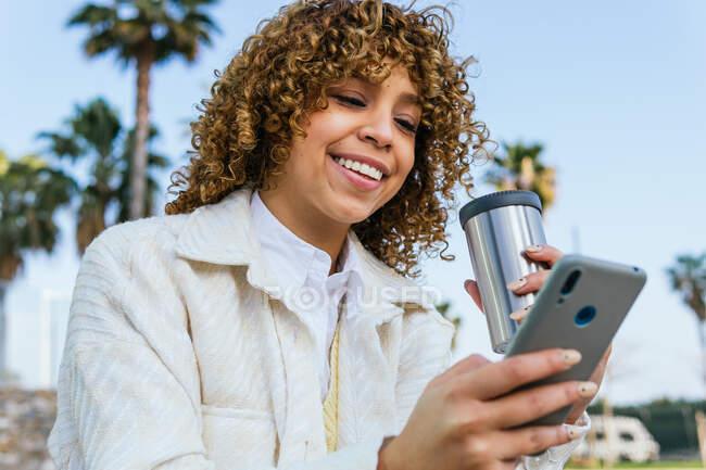 Знизу додатні афроамериканські жінки з кучерявим волоссям, які тримають кавові повідомлення в соціальних мережах через смартфон на вулицях міста. — стокове фото