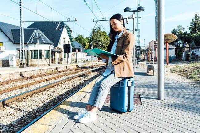 Посмішка азіатська жінка-підприємець читає документи, сидячи на валізі на залізничній станції і чекаючи виїзду. — стокове фото