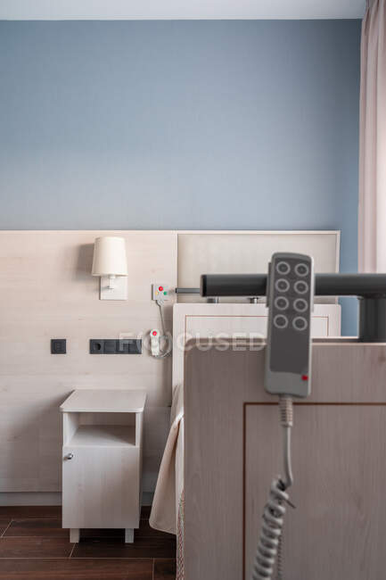 Remote controller hanging on medical bed in bright spacious room in modern hospital — Stock Photo
