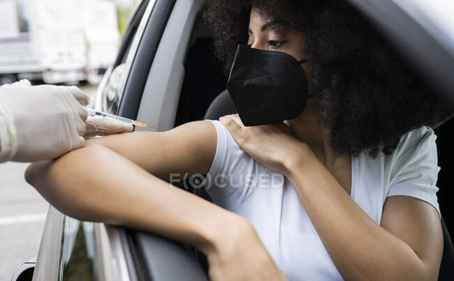 Cropped unrecognizable nurse in latex gloves and uniform vaccinating African American female patient inside the car on a drive through mobile clinic during coronavirus outbreak — Stock Photo