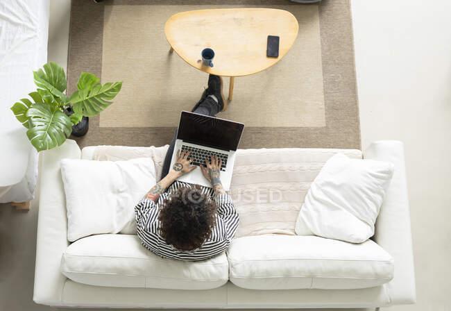 Giovane hipster maschio con capelli ricci navigazione internet su netbook mentre riposava sul divano in camera — Foto stock