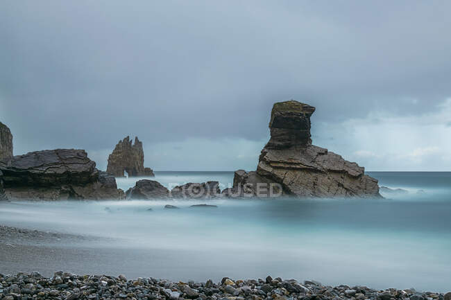 Magnificent view of rough rocks on Portizuelo beach under cloudy sky on overcast day in Asturias — Stock Photo