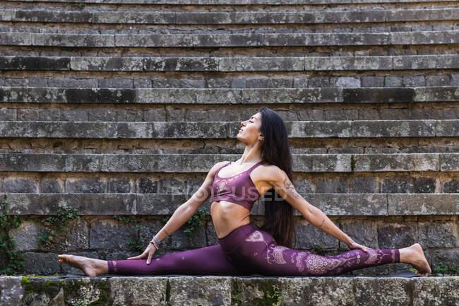 Вид сбоку гибкой женщины в активаторе, сидящей в Хануманасане по каменной лестнице и растягивающей тело во время занятий йогой — стоковое фото
