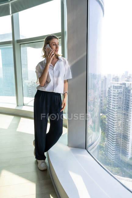 Young businesswoman standing in office with big windows having a phone call on the mobile phone — Stock Photo