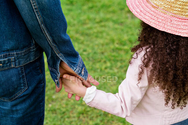 Adult ethnic dad walking with girl against blooming almond trees in park — Stock Photo