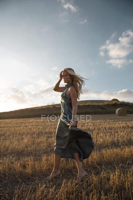 Mujer pacífica en vestido elegante de pie en el campo seco en la zona rural y los ojos cerrados - foto de stock