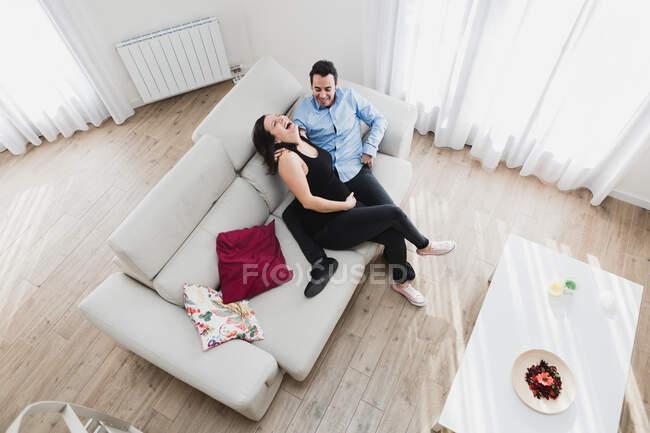 Сверху радостная беременная женщина, сидящая на диване с мужчиной, наслаждаясь выходными вместе дома — стоковое фото