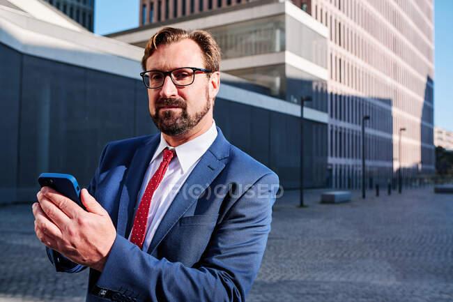 Ernsthafter männlicher Manager im Anzug steht in der Innenstadt und surft mit dem Handy im Internet — Stockfoto