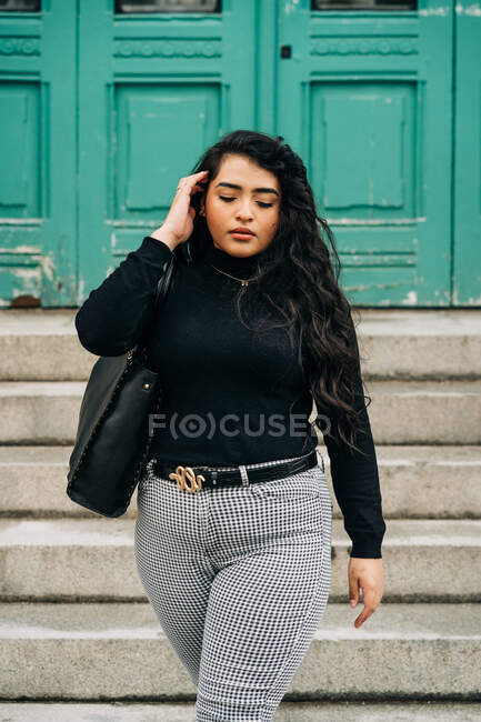 Charming curvy female in trendy outfit walking in city street and touching long wavy hair — Stock Photo