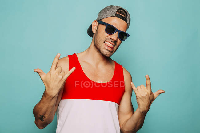 Rebel young ethnic hipster man in cap and black sunglasses with tongue out showing sign of horns while standing against blue background — Stock Photo