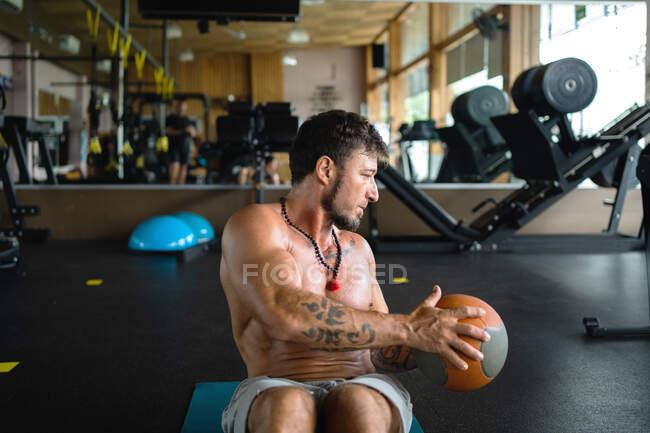 Hombre atlético con torso desnudo sudoroso entrenando con balón de medicina y haciendo giros abdominales durante el entrenamiento en el gimnasio - foto de stock