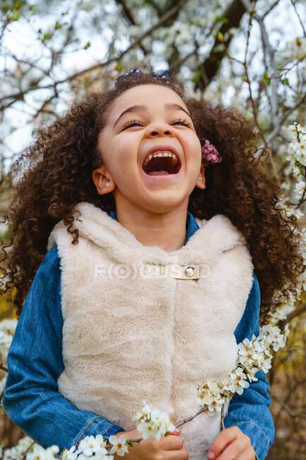 Enfant amical avec les cheveux bouclés et la plante en fleurs brin regardant vers le haut dans la journée sur fond flou — Photo de stock