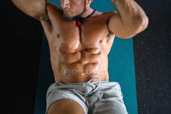 Desde arriba de macho fuerte enfocado con torso desnudo haciendo abdominales crujidos mientras entrena en el gimnasio - foto de stock