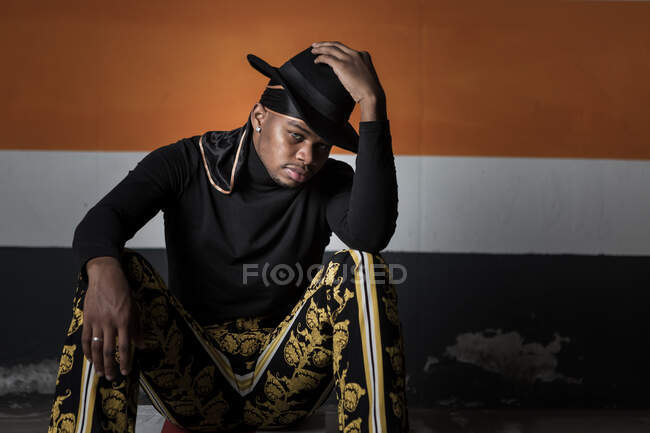 Black male model wearing trendy hat and fancy outfit hunkering in dark underground parking — Stock Photo