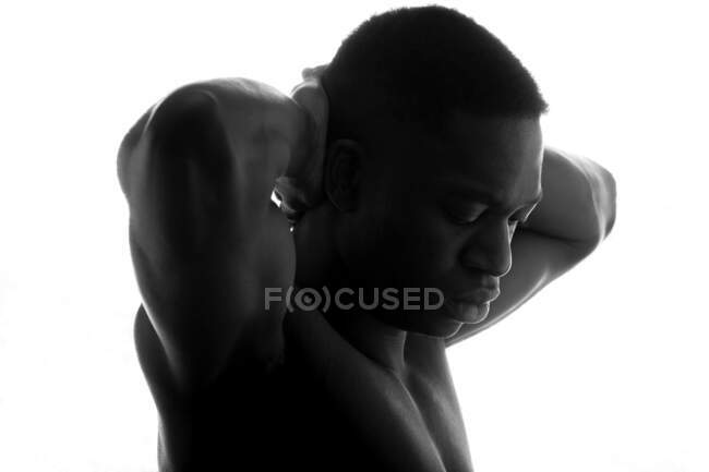 Black and white side view of serious young shirtless athletic African American guy with hands behind back and closed eyes on white background in studio — Stock Photo