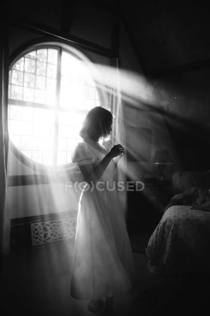Чорно-білий вид нерозпізнаної жінки в сукні, що стоїть проти круглої форми вікна в будинку в сонячний день — стокове фото