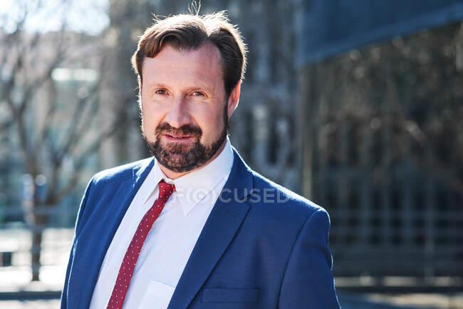 Неголений чоловік-виконавчий у костюмі краватки дивиться на камеру, що стоїть на вулиці — стокове фото