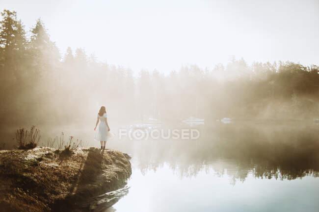 Mujer vista trasera vestida con un vestido blanco en una roca mirando a un lago en un día de niebla - foto de stock