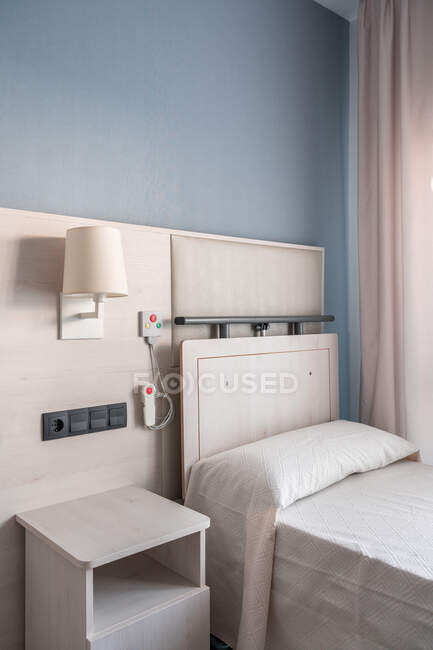 Nurse call system with emergency buttons installed near bed in minimalist medical room interior in hospital — Stock Photo