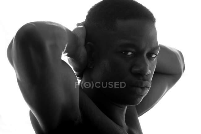 Vista lateral en blanco y negro de un joven serio sin camisa atlético afroamericano con las manos detrás de la espalda y mirando a la cámara en el fondo blanco en el estudio - foto de stock