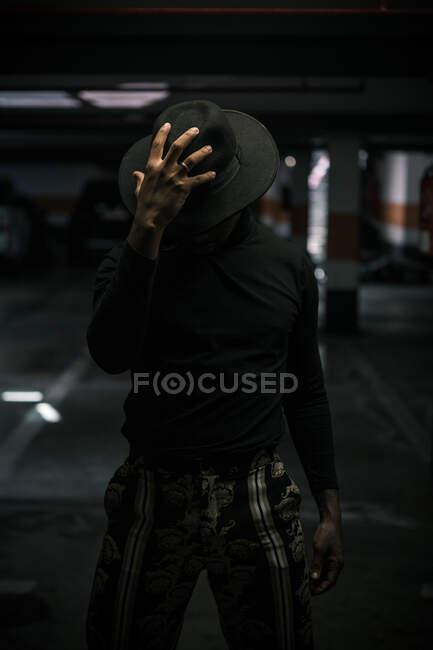 Нерозпізнаний афроамериканець, який торкається модного капелюха, стоячи в темному підземному парковці. — стокове фото