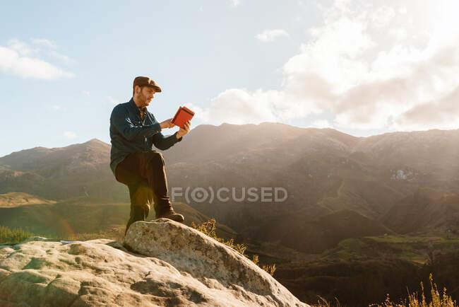 Спокійний самець - дослідник з табличкою, що стоїть на скелі і має захопливий вид на гори в сонячний день. — стокове фото