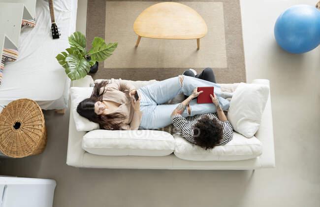 Високий кут жіночих повідомлень на мобільному телефоні, відпочиваючи на дивані з татуюванням коханого чоловіка вдома. — стокове фото