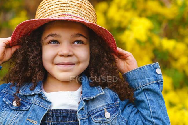 Ragazzo sorridente con capelli ricci e cappello di paglia che distoglie lo sguardo dall'arbusto fiorito con fiori gialli in giardino — Foto stock