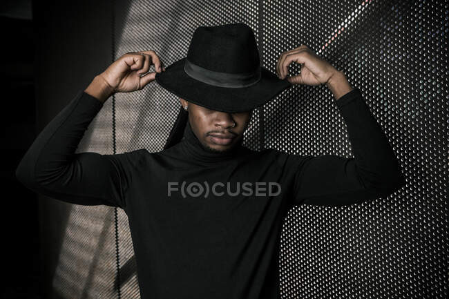 Unrecognizable African American male touching trendy hat while standing in dark underground parking — Stock Photo