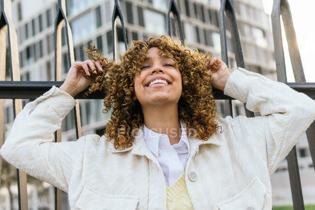 Side view of charming smiling black female with curly hair leaning on metal fence in city with eyes closed — Stock Photo