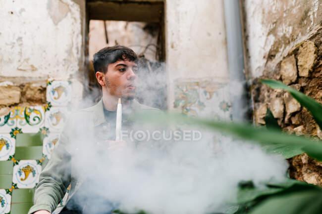 Calma macho fumar cigarrillo electrónico y exhalar el humo mientras se relaja y mirar hacia otro lado - foto de stock