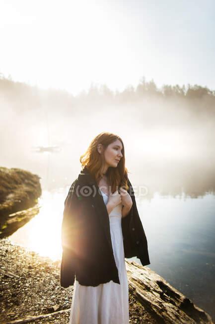 Mujer de pie vestida con un vestido blanco y una chaqueta sobre ella en una roca mirando a un lago en un día de niebla - foto de stock