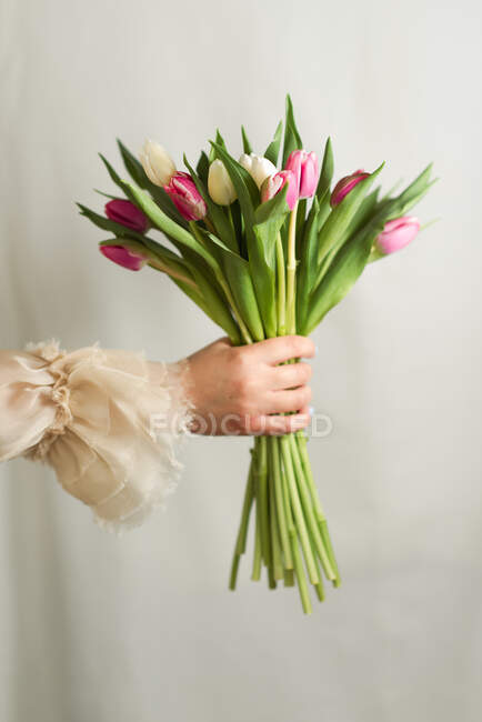 Crop unrecognizable female in romantic dress standing with bunch of tender colorful flowers — Stock Photo