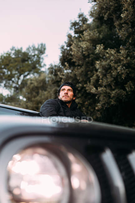 Знизу шукач пригод спирається на двері позашляховика, дивлячись у далечінь перед початком подорожі — стокове фото