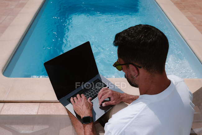 Male freelancer lying on lounger at poolside and surfing Internet on laptop during telework in summer on sunny day — Stock Photo