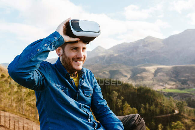 Curious male traveler sitting on hill and experiencing virtual reality in goggles in mountains on sunny day — Stock Photo