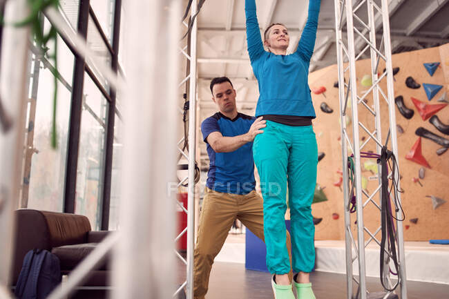 From below of female doing pull ups on horizontal bar with help of instructor while training in modern climbing center — Stock Photo