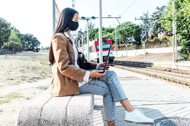 Бічний вид азіатки в масці сидить на лавці на залізничній станції і переглядає ноутбук під час очікування поїзда. — стокове фото