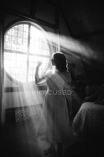 Black and white side view of unrecognizable female in dress standing against round shaped window in house on sunny day — Stock Photo