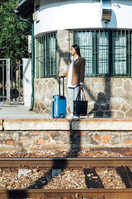 Asian female traveler with suitcase standing on platform of railroad station while waiting for the train — Stock Photo