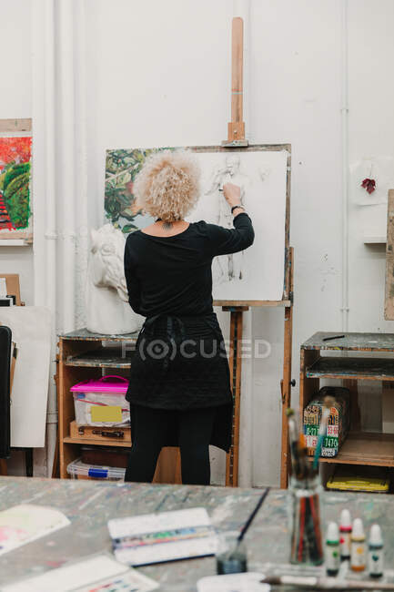 Back view of anonymous female artist creating drawing of human with pencil while standing at easel in studio — Stock Photo