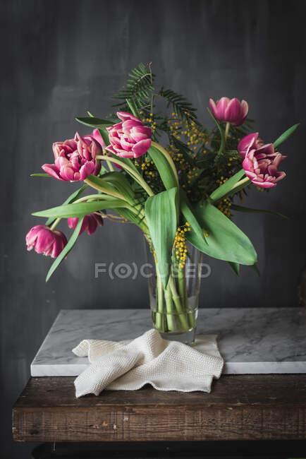 Fleurs roses fleuries avec des pétales doux et des feuilles vertes dans un vase sur fond gris — Photo de stock