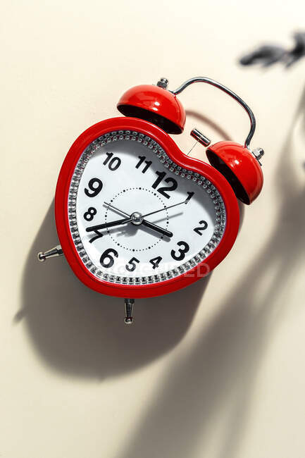 Red metal alarm clock in shape of heart placed on vibrant beige background in studio — Stock Photo