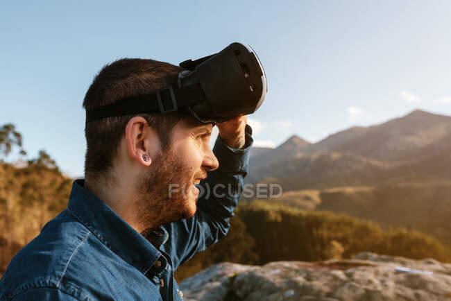 Curioso viajero masculino sentado en la colina y experimentando la realidad virtual en gafas en las montañas en un día soleado - foto de stock