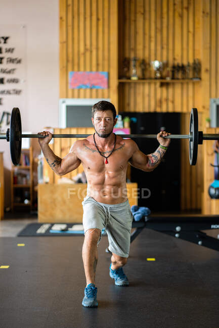 Determined athletic male with naked torso doing walking lunges with barbell during intense workout in gym — Stock Photo