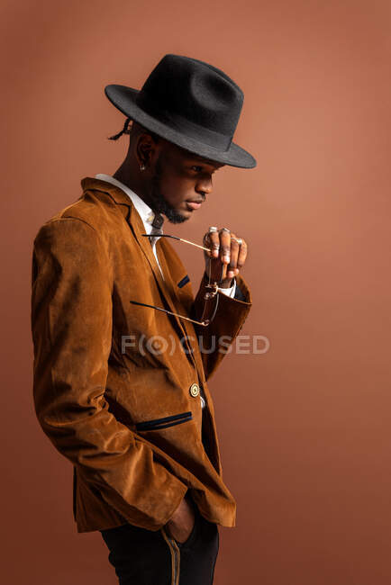 Side view of young African American male in trendy apparel and hat looking away on brown background — Stock Photo