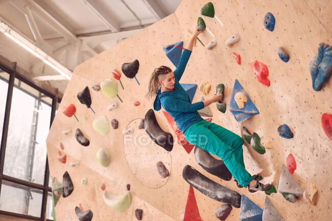 Восхождение на искусственную стену во время боулдеринга в профессиональном спортзале — стоковое фото