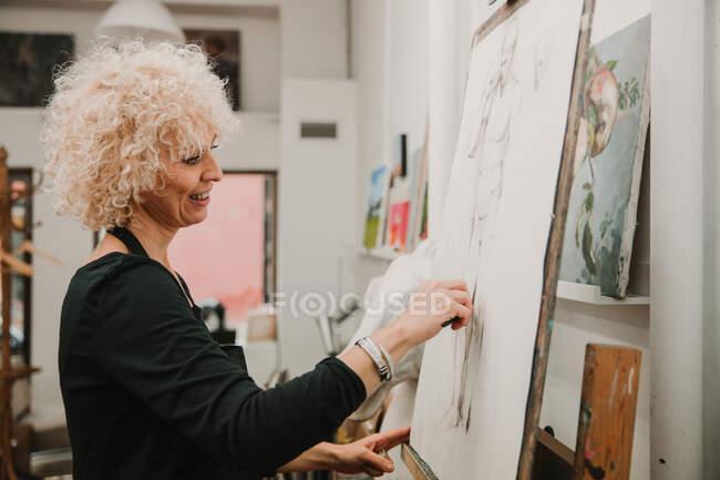 Artista femenina creando dibujo de humano con lápiz mientras está de pie en el caballete en el estudio - foto de stock